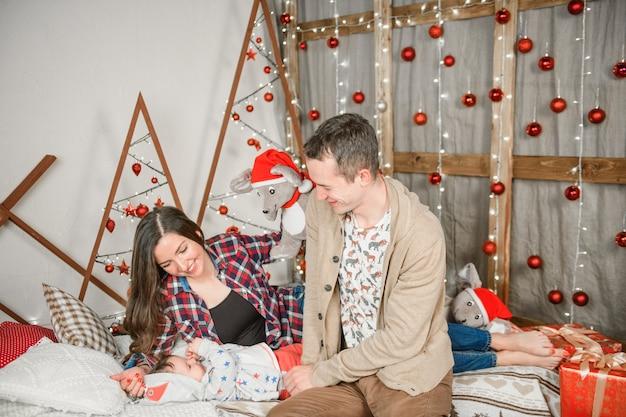 Счастливая семья рождества. счастливая семья на рождество. родители и малыш.