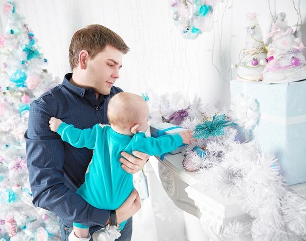 ハッピークリスマス。父は赤ちゃんにクリスマスプレゼントを見せます。父性の概念。