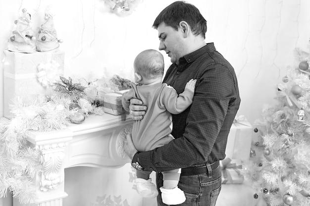 행복한 크리스마스. 아버지는 그의 아기 크리스마스 선물을 보여줍니다. 아버지의 개념.
