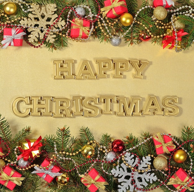 ハッピークリスマスの黄金のテキストとトウヒの枝と黄金の背景にクリスマスの装飾