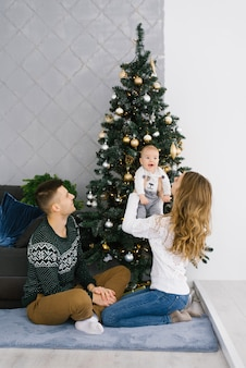 Happy christmas and new year celebration of young family in living room. they sit on the floor near the christmas tree, smiling and happy