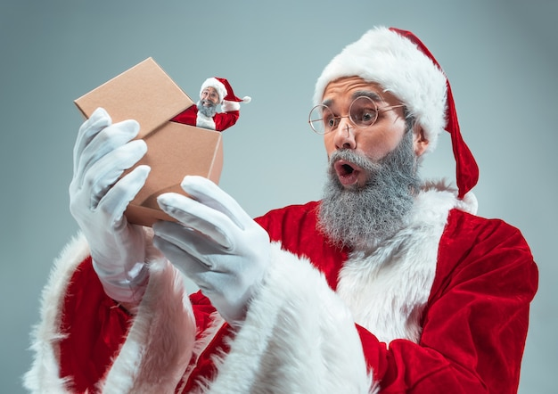 Happy christmas santa claus on grey studio background. caucasian male model in traditional holiday's costume. concept of holidays, new year's, winter mood, gifts. unpacking gifts, wondered.