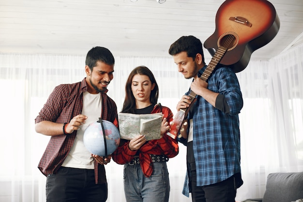 Happy circle of friends planning a trip. globe trotters inspecting a map being at home. european and indian ethnicity. men holding guitar and globe.