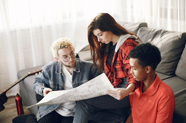 旅行を計画している友人の幸せな輪。家にある地図を調べるグローブトロッター。ヨーロッパとインドの民族。