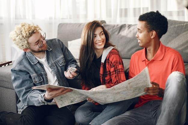 Счастливый круг друзей, планирующих поездку. рысаки земного шара рассматривают карту, находясь дома. европейская и индийская национальность.