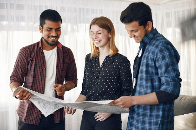 여행을 계획하는 친구의 행복한 원. 집에있는지도를 조사하는 글로브 족보. 유럽과 인도 민족.