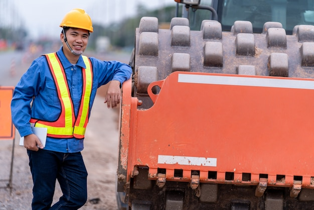 Счастливый инженер-строитель, стоя сбоку желтой вибрирующей почвы на строительной площадке