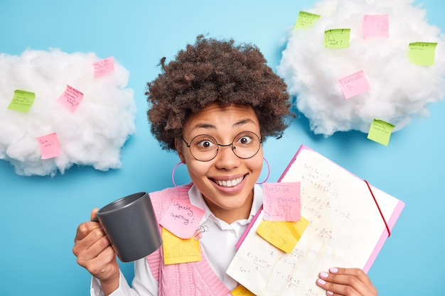 Happy clever afro american student has coffee break prepares for seminar shows notes made during lecture gets ready for exams wears spectacles involved in studying