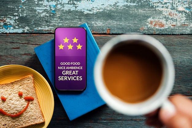 Happy client giving five star rating and positive review on smartphone at cafe or restaurant.