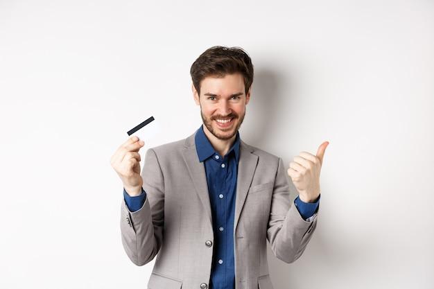 Счастливый клиент в деловом костюме показывает пластиковую кредитную карту и большой палец вверх, удовлетворенно улыбаясь
