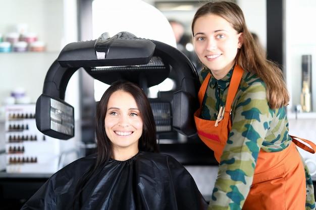 Счастливый клиент сидит на стуле в накидке, сушит волосы и смотрит в сторону возле парикмахерской.
