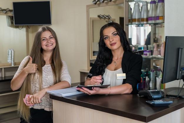Счастливый клиент с администратором возле стойки регистрации