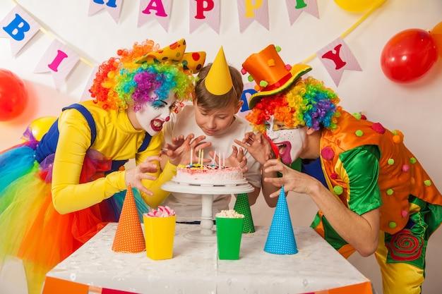 휴일에 행복한 광대가 생일 케이크에 촛불을 불어