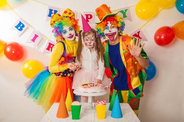 행복한 광대는 휴일에 생일 케이크에 촛불을 불어