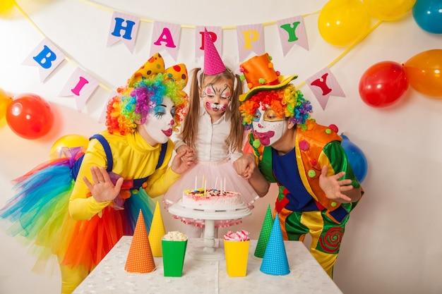 행복한 광대는 휴일에 생일 케이크에 촛불을 불어 프리미엄 사진