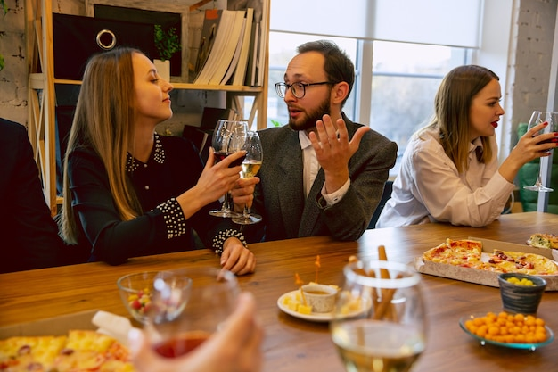 Happy co-workers celebrating while company party, corporate event. young caucasian people in business attire talking, drinking wine. concept of office culture, teamwork, friendship, holidays, weekend.