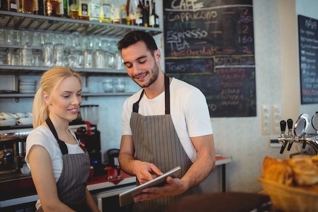 Happy co-workers using digital tablet