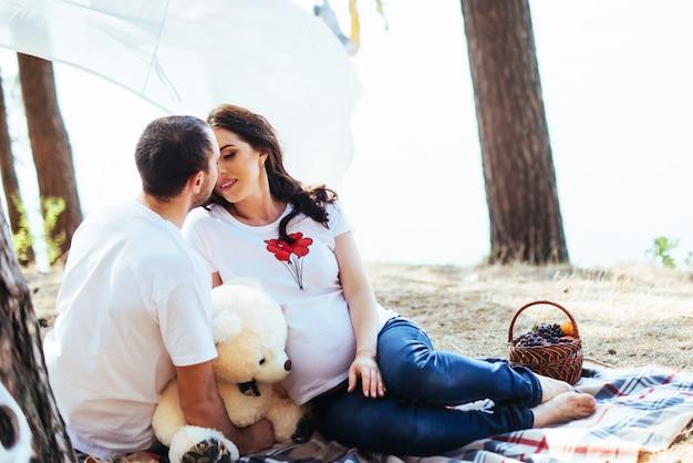 Беременная женщина с мужем на пикник. happy co