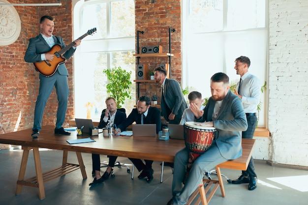 Счастливые коллеги веселятся в офисе, пока их коллеги усердно работают