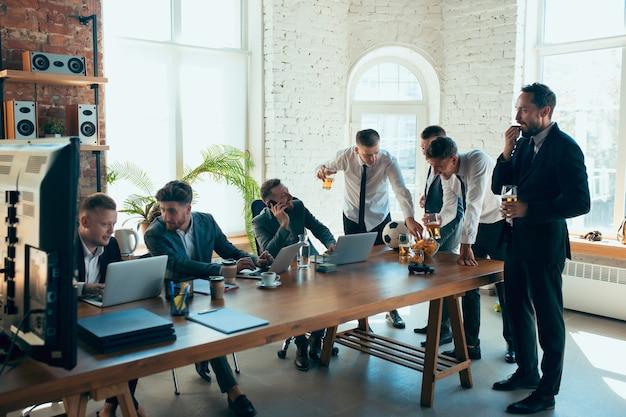 동료들이 열심히 일하는 동안 사무실에서 즐거운 시간을 보내는 행복한 동료들