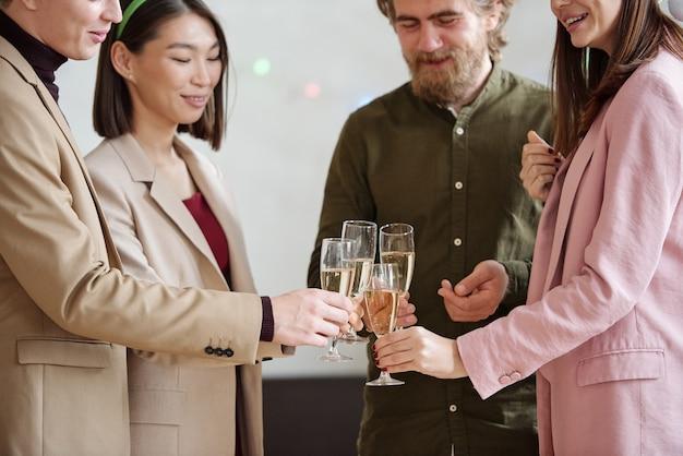 새로운 비즈니스 프로젝트와 파티에서 크리스마스를 위해 건배하는 동안 스마트 캐주얼웨어를 입은 행복한 동료들
