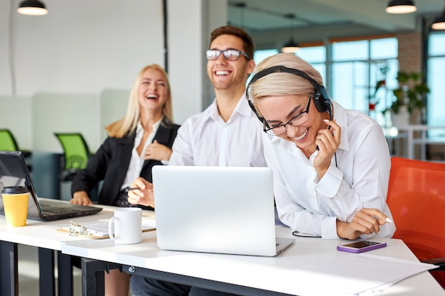 Happy colleagues laughing at work place, caucasian man and women sit with laptop having fun, take a break. focus on blonde female in headphones