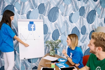 Happy colleagues looking at facebook chart