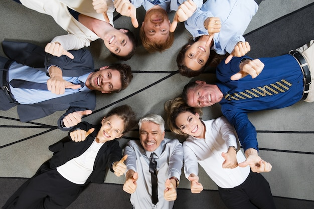 I colleghi felici sdraiato sul pavimento, mostrando thumbs up