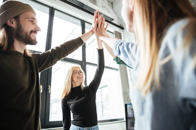 Happy colleagues in office give high five to each other