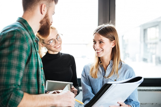 Happy colleagues in office talking with each other holding folder