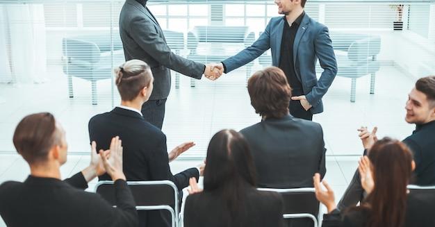 Счастливые коллеги пожимают друг другу руки. встречи и партнерства