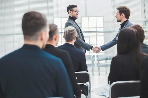 幸せな同僚がお互いに握手します。会議とパートナーシップ