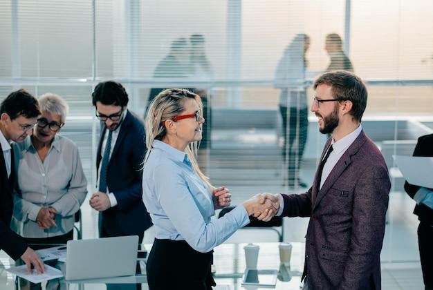 Счастливые коллеги пожимают друг другу руки возле рабочего стола