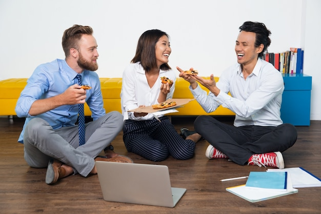 Happy colleagues sitting on floor and eating pizza