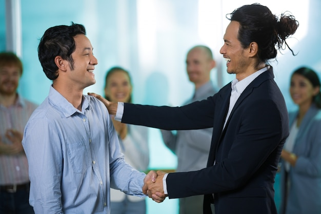 Happy colleagues talking while shaking hands