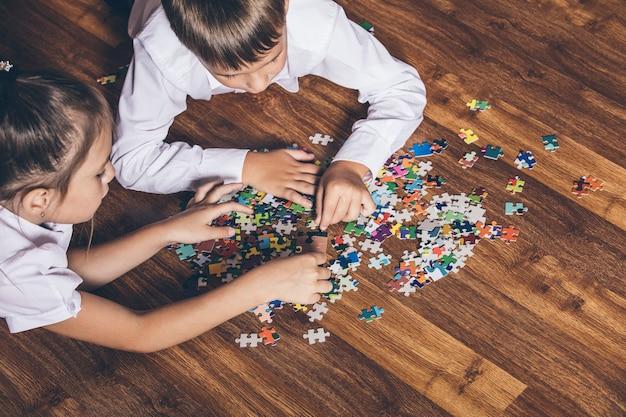 Счастливый собирать головоломку, лежа на полу крупным планом