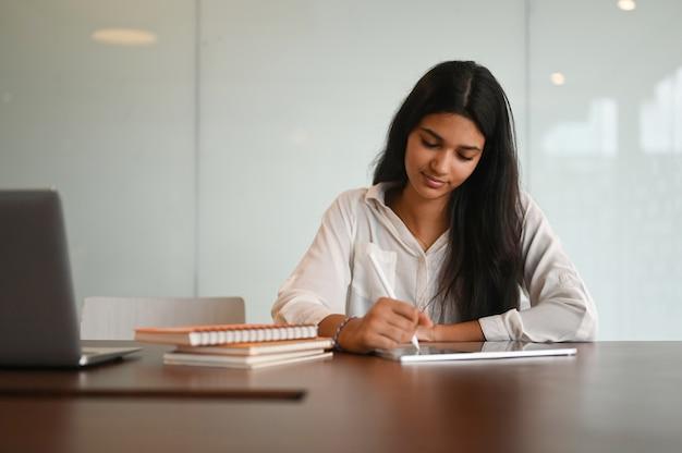 Счастливая девушка колледжа работает над своим заданием с планшетом и стилусом в современной гостиной