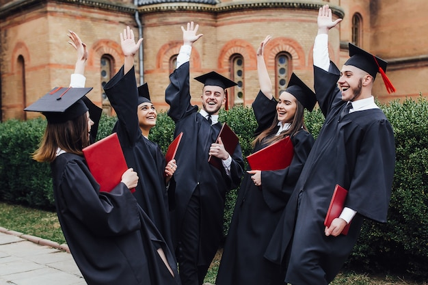 Счастливые выпускники колледжа показывают дипломы на церемонии возле университета