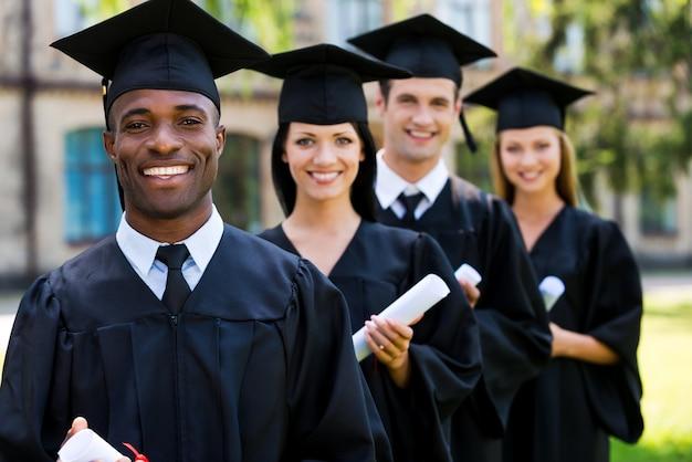 幸せな大学卒業生。 4人の大学卒業生が一列に並んで笑っている