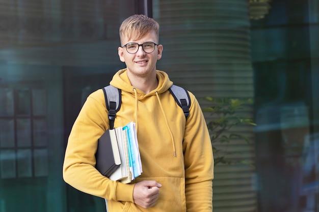 メガネの本とバックパックで幸せな大学生