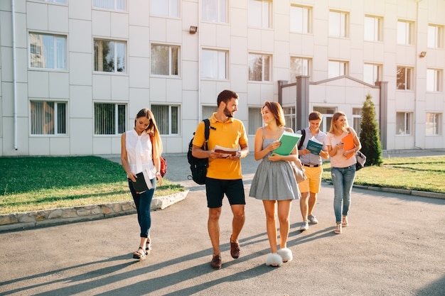 Happy college students with books in hands walking together on campus