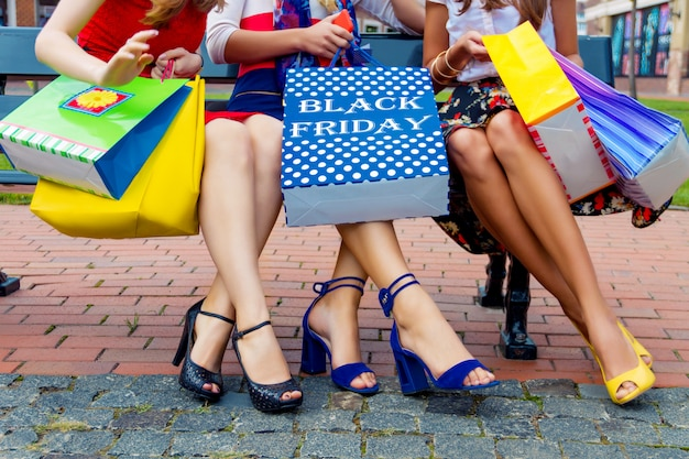 Happy colorful women females adults girls friends legs in colorful dresses sitting outdoor after shopping in shopping mall with packages of shop's goods.