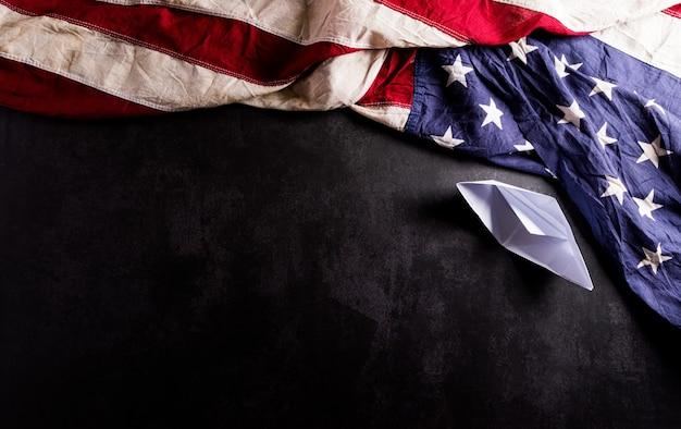 해피 콜럼버스 데이 개념 어두운 돌에 종이 보트와 빈티지 미국 국기