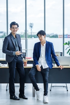 Happy company young asian businessman and coaching personal secretary assistant tomboy lesbian and lgbt partners while working together with laptop computer and strategy in business in office