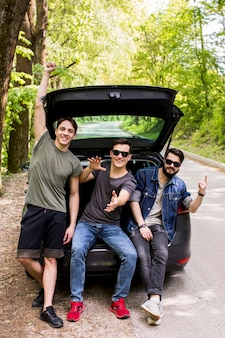 Happy company of young guys sitting in trunk in travel