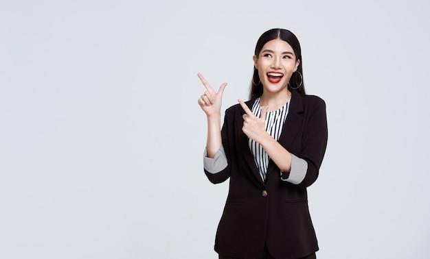 灰色の背景の横にある空白のスペースに指を指している幸せな自信を持ってアジアのビジネス女性