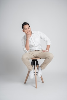 Happy confident asian man relaxing while sitting on the chair