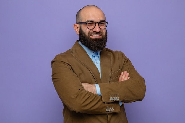 Happy and confident bearded man in brown suit wearing glasses looking at camera smiling cheerfully with arms crossed standing over purple background