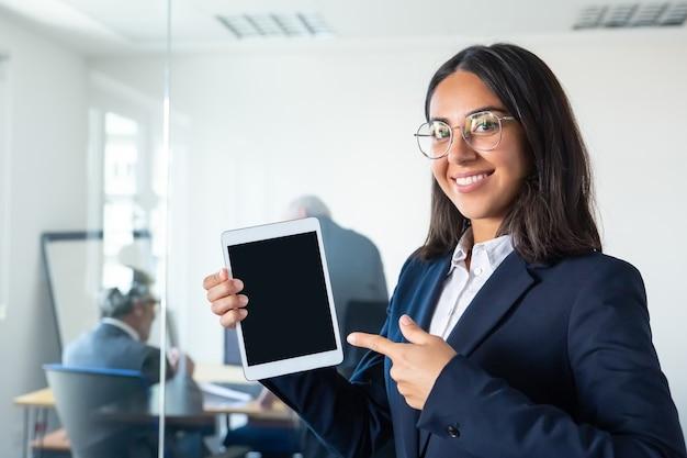 태블릿을 들고, 표시 및 빈 화면에서 손가락을 가리키는, 카메라를보고 웃 고 행복 확신 비즈니스 아가씨. 공간을 복사하십시오. 커뮤니케이션 및 광고 개념