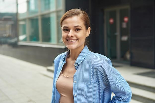 현대적인 사무실 센터에서 걸어 나오는 행복한 자신감 있는 비즈니스 여성. 스마트 캐주얼 야외에서 성공적인 기업가의 초상화.